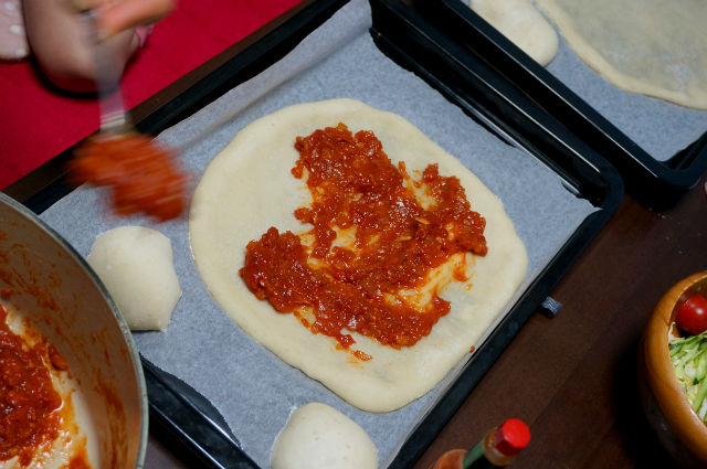 ピザ生地にトマトソースを塗る